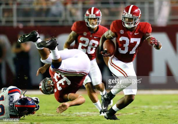 Trey DePriest of the Alabama Crimson Tide is upended by Donte Moncrief of the Mississippi Rebels as Robert Lester returns an interception intended...