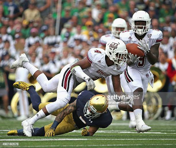 Trey Dudley-Giles of the Massachusetts Minutemen intercepts a pass tipped by teammate Randall Jette against the Notre Dame Fighting Irish that was...