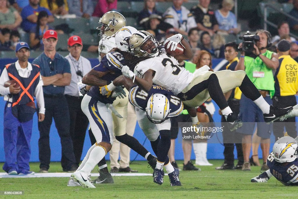 Trey Edmunds #33 of the New Orleans Saints goes over the top of Randall Evans #41 of the Los Angeles Chargers for extra yardage during the game between the Los Angeles Chargers and the New Orleans Saints at the StubHub Center on August 20, 2017 in Carson, California.
