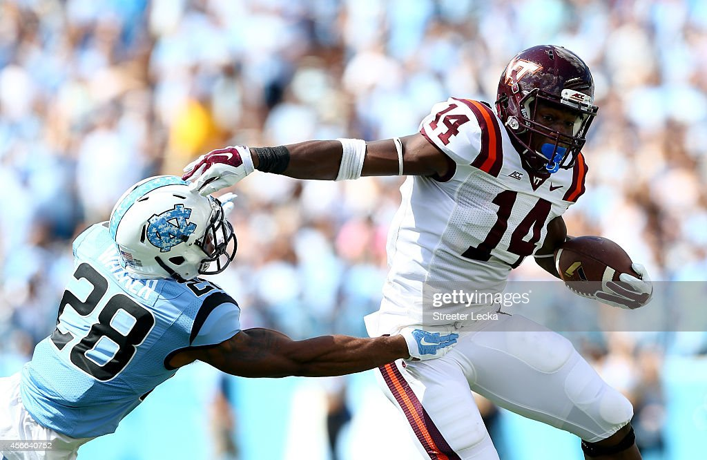 Trey Edmunds #14 of the Virginia Tech Hokies tries to get away from Brian Walker #28 of the North Carolina Tar Heels during their game at Kenan Stadium on October 4, 2014 in Chapel Hill, North Carolina.