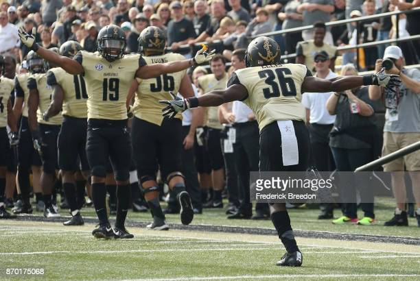 Trey Ellis of the Vanderbilt Commodores celebrates with teammate CJ Duncan after scoring a touchdown by catching a deflected pass against the Western...