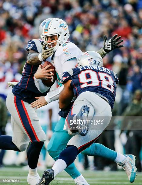 Trey Flowers and Marquis Flowers of the New England Patriots tackle Matt Moore of the Miami Dolphins during the third quarter of a game at Gillette...