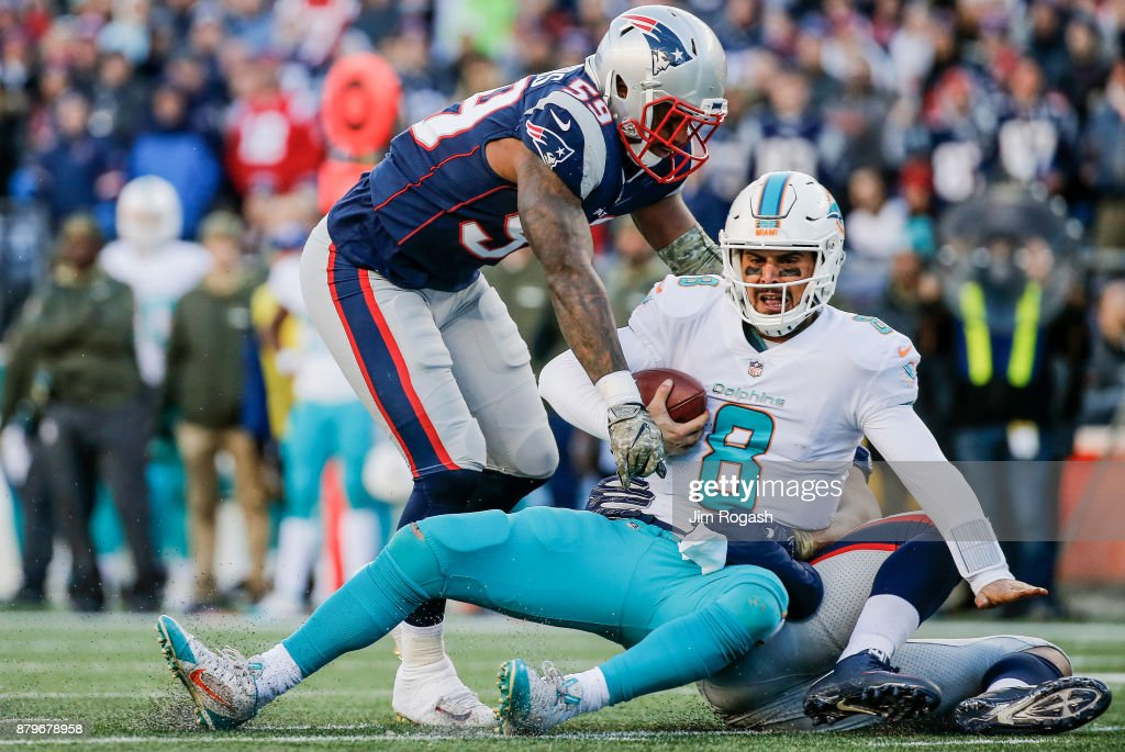 Trey Flowers #98 and Marquis Flowers #59 of the New England Patriots tackle Matt Moore #8 of the Miami Dolphins during the third quarter of a game at Gillette Stadium on November 26, 2017 in Foxboro, Massachusetts.