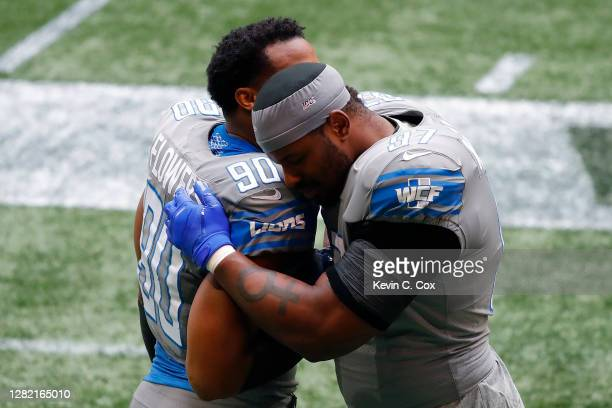 Trey Flowers and Nick Williams of the Detroit Lions embrace prior to the game against the Atlanta Falcons at Mercedes-Benz Stadium on October 25,...