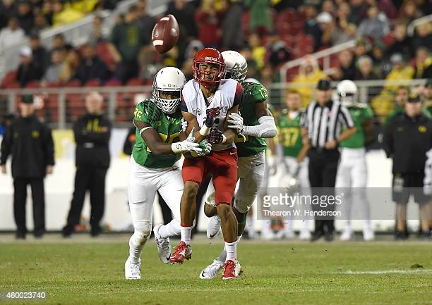 Trey Griffey of the Arizona Wildcats is sandwiched by Torrodney Prevot of the Oregon Ducks and Troy Hill of the Oregon Ducks in the first half of the...