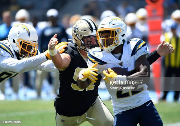 Trey Hendrickson of the New Orleans Saints unable to tackle running back Justin Jackson of the Los Angeles Chargers during the first half of their...