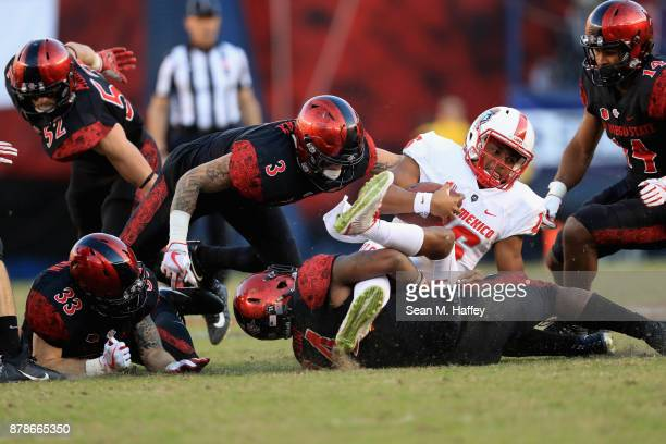 Trey Lomax Parker Baldwin and Tariq Thompson of the San Diego State Aztecs tackle Tevaka Tuioti of the New Mexico Lobos during the second half of a...