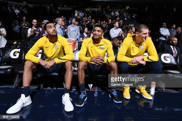 Trey Lyles Gary Harris and Mason Plumlee of the Denver Nuggets look on from the bench during the game against the Phoenix Suns on January 19 2018 at...