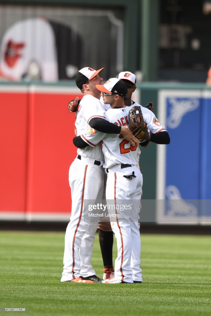 Trey Mancini #16, Adam Jones #10 and Joey Rickard #23 of the Baltimore Orioles celebrate a win after a baseball game against the Tampa Bay Rays at Oriole Park at Camden Yards on July 29, 2018 in Baltimore, Maryland.