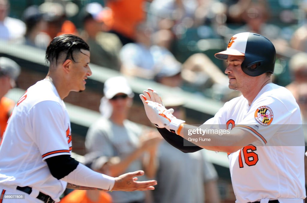 Trey Mancini #16 of the Baltimore Orioles celebrates with Manny Machado #13 after hitting a home run in the fifth inning against the Los Angeles Angels at Oriole Park at Camden Yards on July 1, 2018 in Baltimore, Maryland.