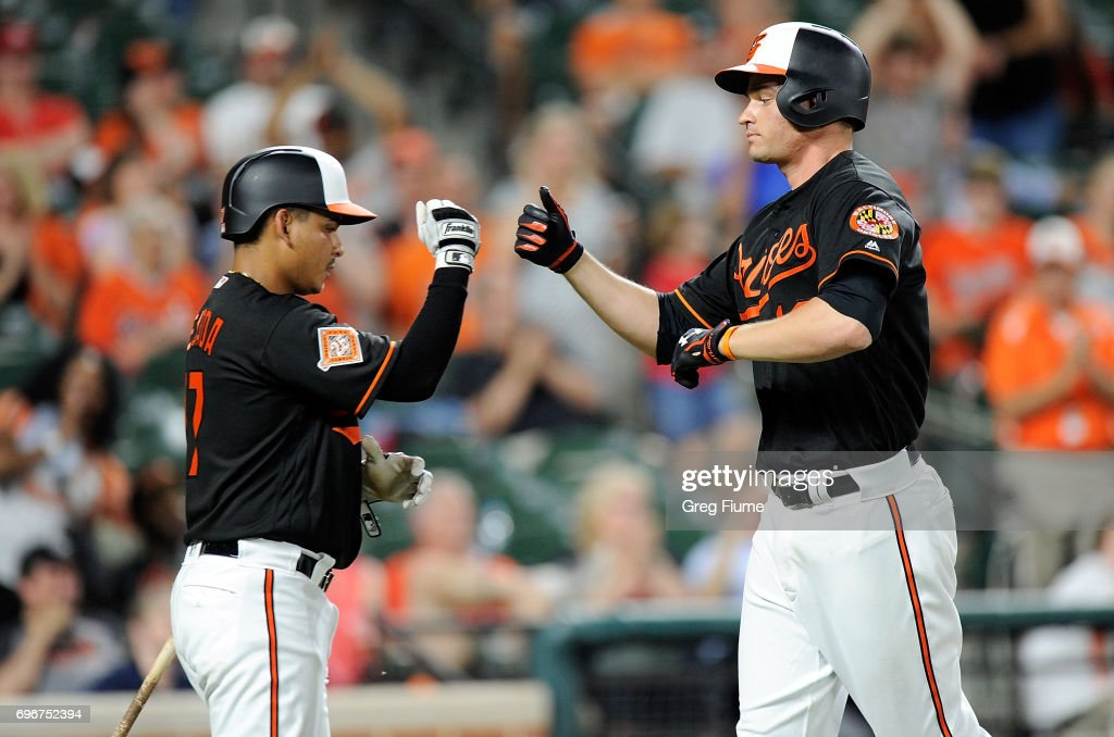 Trey Mancini #16 of the Baltimore Orioles celebrates with Ruben Tejada #17 after hitting a home run in the ninth inning against the St. Louis Cardinals at Oriole Park at Camden Yards on June 16, 2017 in Baltimore, Maryland.