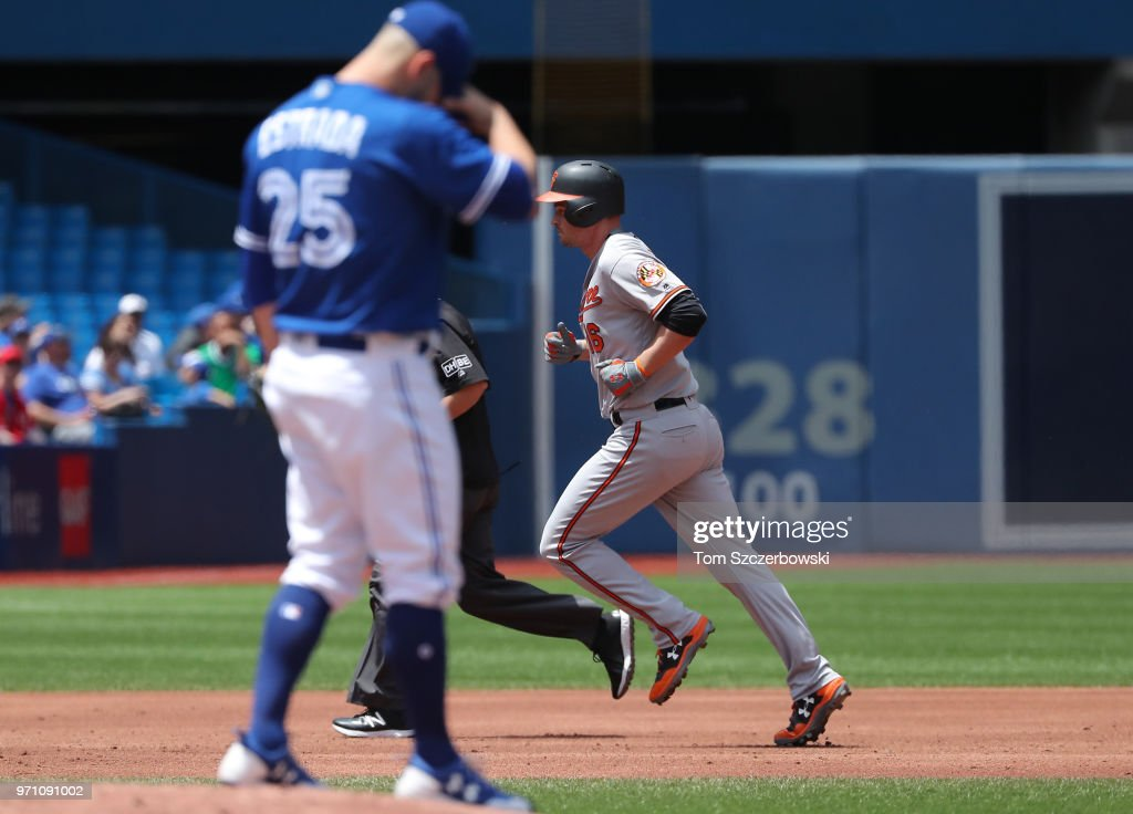 Trey Mancini #16 of the Baltimore Orioles circles the bases after hitting a solo home run as Marco Estrada #25 of the Toronto Blue Jays reacts in the second inning during MLB game action at Rogers Centre on June 10, 2018 in Toronto, Canada.