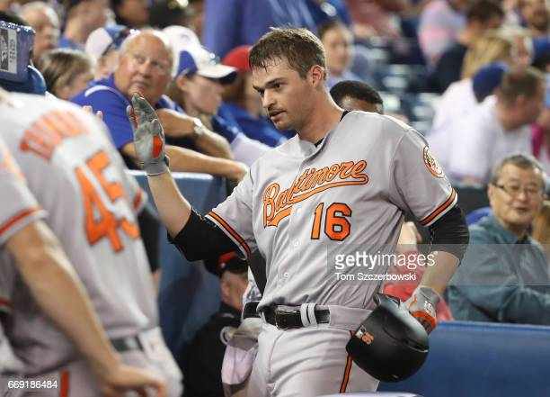 Trey Mancini of the Baltimore Orioles is congratualted by teammates in the dugout after hitting his second home run of the game a solo home run in...