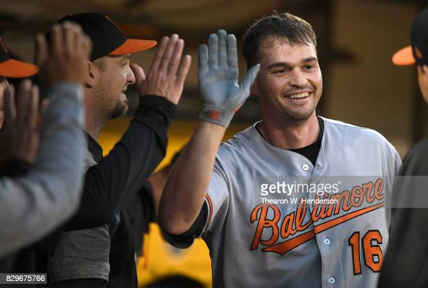 Trey Mancini of the Baltimore Orioles is congratulated by teammates after he hit a solo home run against the Oakland Athletics in the top of the...