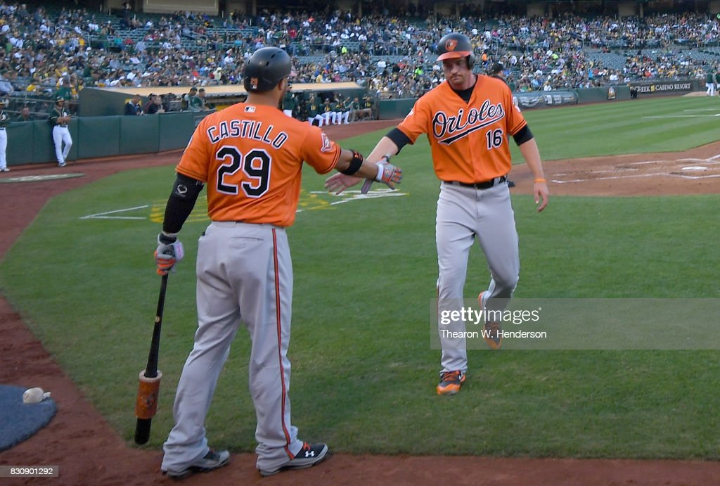 Trey Mancini #16 of the Baltimore Orioles is congratulated by Welington Castillo #29 after Mancini scored against the Oakland Athletics in the top of the first inning at Oakland Alameda Coliseum on August 12, 2017 in Oakland, California.