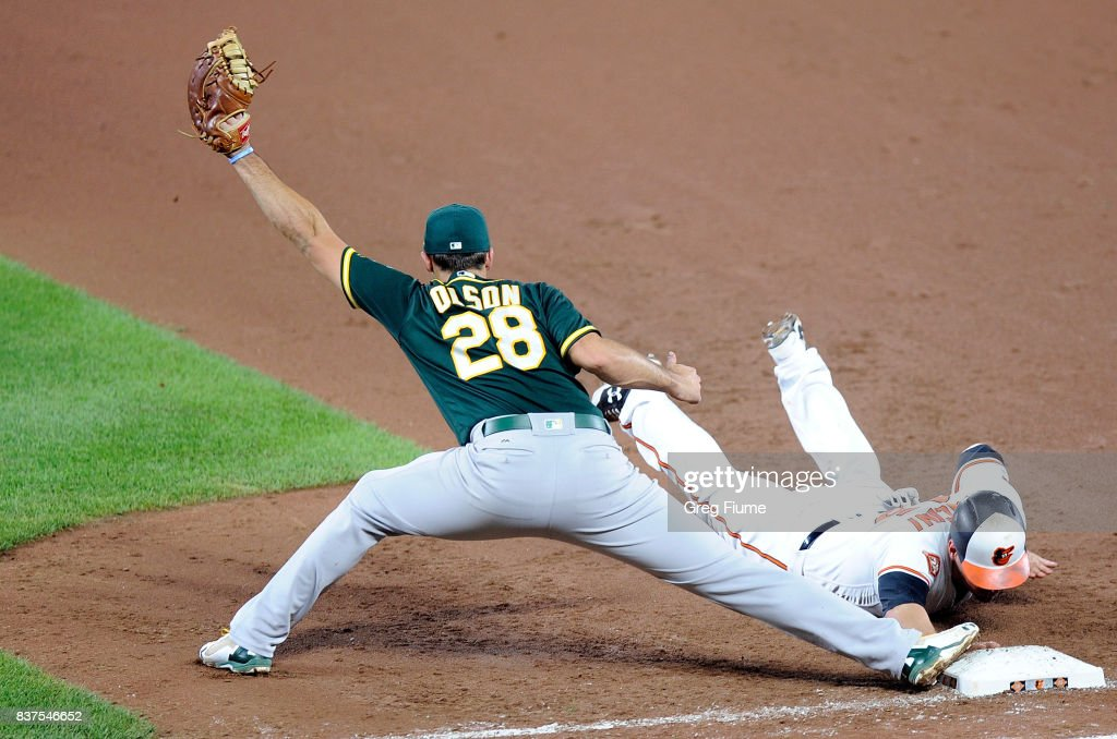 Trey Mancini #16 of the Baltimore Orioles is doubled off of first base in the fifth inning by Matt Olson #28 of the Oakland Athletics at Oriole Park at Camden Yards on August 22, 2017 in Baltimore, Maryland.