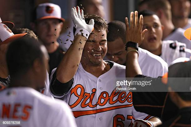 Trey Mancini of the Baltimore Orioles is greeted in the dugout by teammates after hitting a home run during the fifth inning against the Boston Red...