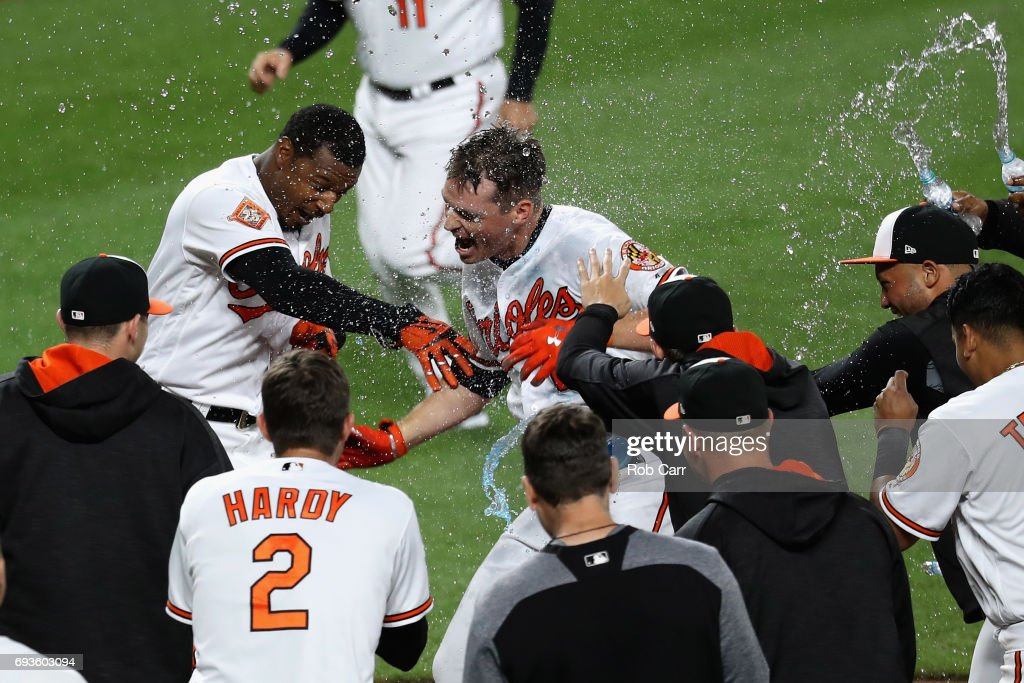 Trey Mancini #16 of the Baltimore Orioles is mobbed by teammates at home plate after hitting a walk off three run homer to defeat the Pittsburgh Pirates 9-6 in eleven innings at Oriole Park at Camden Yards on June 7, 2017 in Baltimore, Maryland.