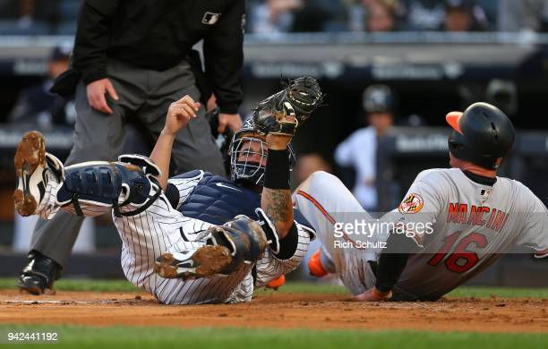 Trey Mancini of the Baltimore Orioles is tagged out at the plate by catcher Gary Sanchez of the New York Yankees attempting to score on a hit by Adam...
