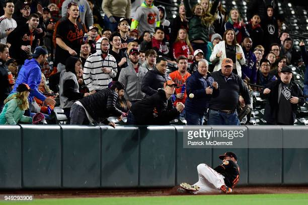 Trey Mancini of the Baltimore Orioles is unable to catch a fly ball hit by Yonder Alonso of the Cleveland Indians in the eighth inning at Oriole Park...
