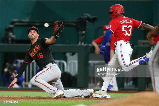 Trey Mancini of the Baltimore Orioles is unable to come up with the ball as Adolis Garcia of the Texas Rangers reaches first in the ninth inning at...