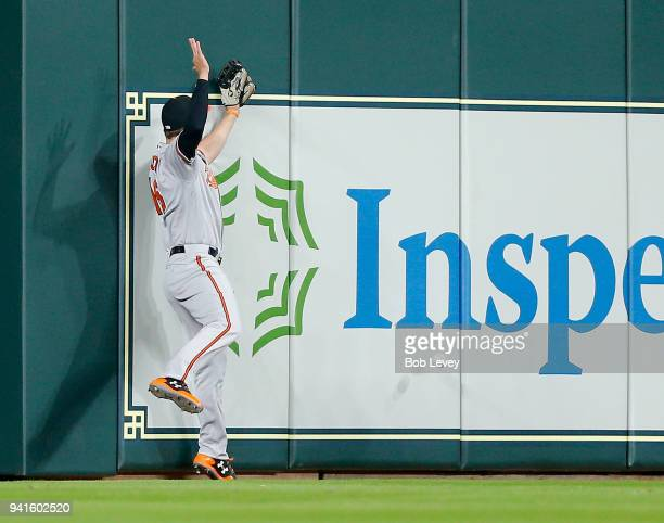 Trey Mancini of the Baltimore Orioles leaps at the wall but is unable to catch a ball hit by Carlos Correa of the Houston Astros in the first inning...