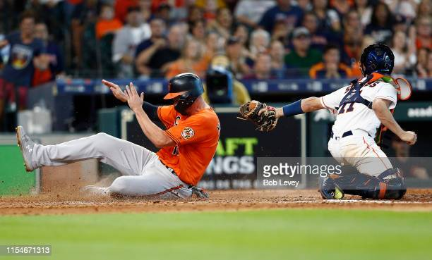 Trey Mancini of the Baltimore Orioles scores in the eighth inning as Garrett Stubbs of the Houston Astros is unable to make the tag at Minute Maid...