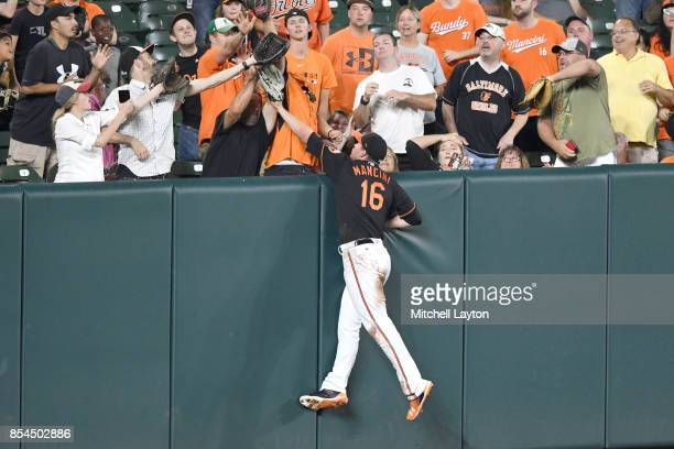Trey Mancini of the Baltimore Orioles tries to catcha fly ball during a baseball game against the Tampa Bay Rays at Oriole Park at Camden Yards on...