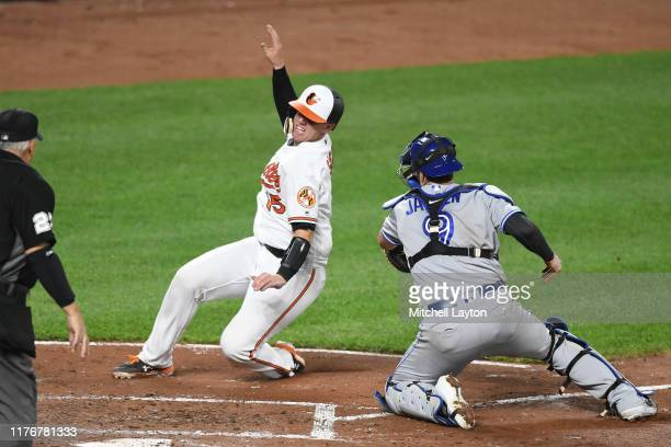 Trey Mancini of the Baltimore Orioles tries to get around Danny Jansen of the Toronto Blue Jays at home plate during a baseball game at Oriole Park...