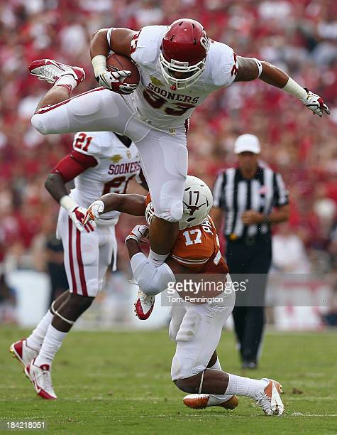 Trey Millard of the Oklahoma Sooners carries the ball against Adrian Phillips of the Texas Longhorns in the first quarter at the Cotton Bowl on...