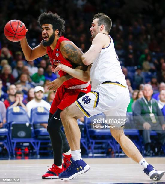 Trey Moses of the Ball State Cardinals dribbles around John Mooney of the Notre Dame Fighting Irish at Purcell Pavilion on December 5 2017 in South...