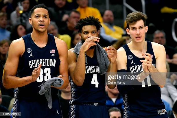 Trey Mourning Jagan Mosely and Greg Malinowski of the Georgetown Hoyas look on from the bench during the game against the Marquette Golden Eagles at...