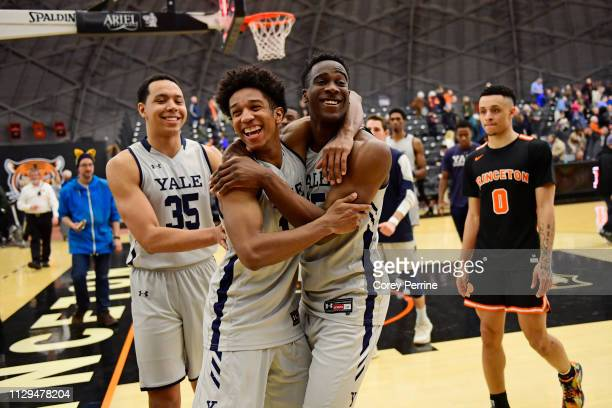 Trey Phills and Miye Oni of the Yale Bulldogs hug reacting to the win as teammate Isaiah Kelly and Jaelin Llewellyn of the Princeton Tigers look on...