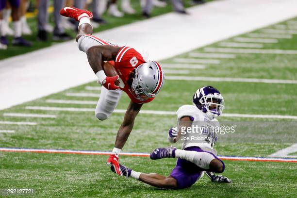 Trey Sermon of the Ohio State Buckeyes gets upended by A.J. Hampton of the Northwestern Wildcats in the first quarter of the Big Ten Championship at...