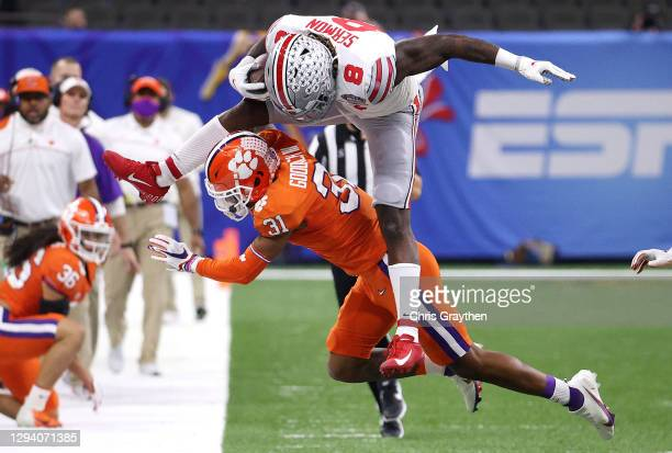 Trey Sermon of the Ohio State Buckeyes hurdles Mario Goodrich of the Clemson Tigers in the first quarter during the College Football Playoff...