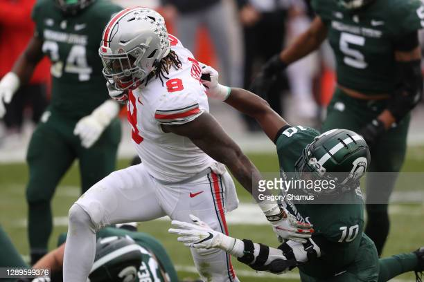 Trey Sermon of the Ohio State Buckeyes tries to escape the tackle of Michael Dowell of the Michigan State Spartans during a first half run at Spartan...