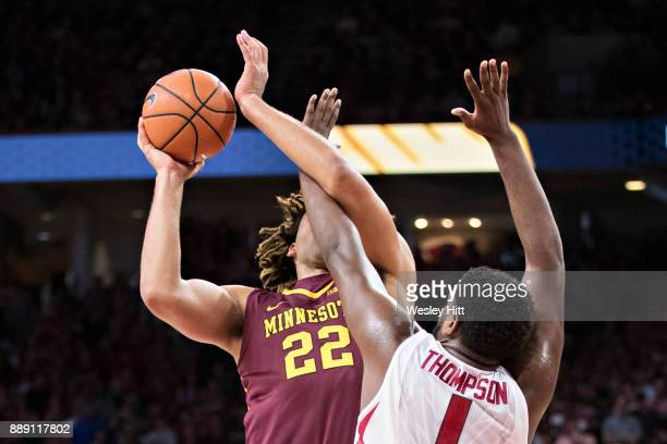 Trey Thompson of the Arkansas Razorbacks gets tangled up with Reggie Lynch of the Minnesota Golden Gophers at Bud Walton Arena on December 9 2017 in...