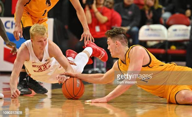 Trey Woodbury of the UNLV Rebels and Hunter Thompson of the Wyoming Cowboys scramble for a loose ball during the first half of their game at the...