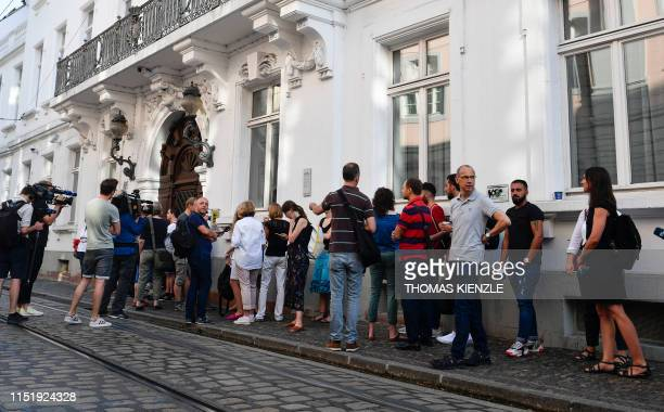 Trial observers line up to enter the district court in Freiburg, southern Germany, on June 26 on the first day of a trial against eleven defendants....