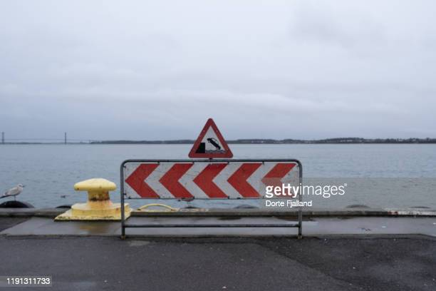triangle road sign with a red border warning that cars can fall into the water. - dorte fjalland stock pictures, royalty-free photos & images