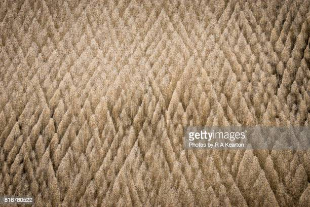 Triangular sand patterns on beach