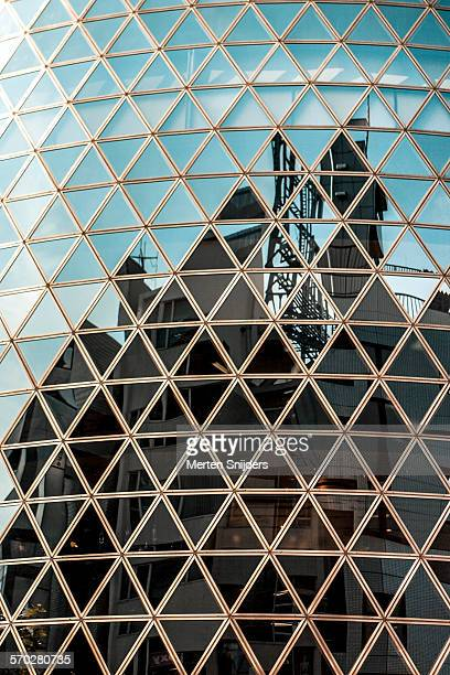 Triangular windows with city reflections