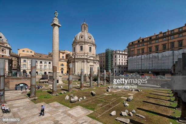 trianna square with ruins and coloumn with crowds and santa maria di loreto church at the background in rome. - emreturanphoto stock pictures, royalty-free photos & images