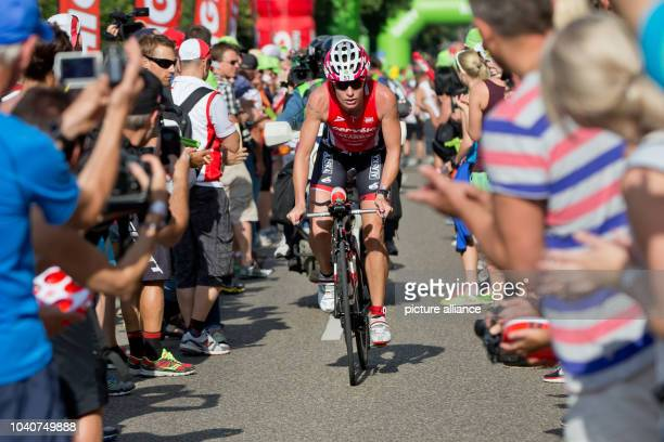 Triathlete Caroline Steffen of Switzerland rides on her bicycle past a cheering crowd of spectators during the Datev Challenge Roth in Hilpoltstein...