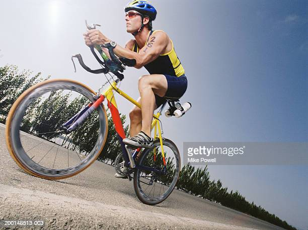 Triathlete riding bicycle down road in triathlon