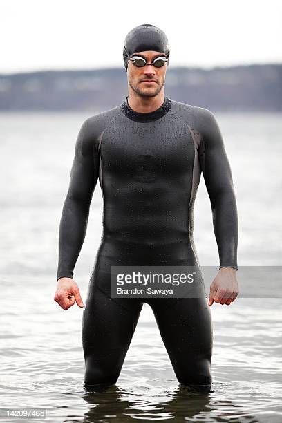A triathlete stands ready for his swim.