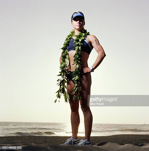 Triathlete wearing ti leaf lei, standing on beach, portrait