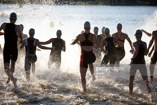 Triathletes At Start of Triathlon Running Into The Water.
