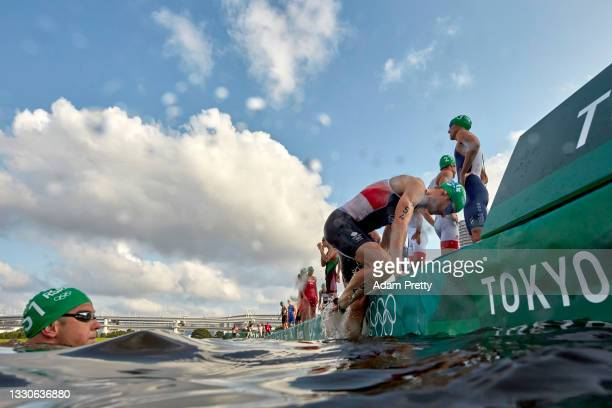 Triathletes climb back onto shore after a broadcast boat in the water forced a restart before the Men's Individual Triathlon on day three of the...