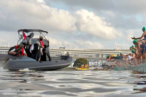 Triathletes dive into the water as a broadcast boat prevents all swimmers from starting forcing a restart before the Men's Individual Triathlon on...